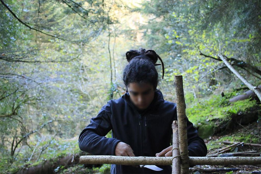 Un jeune homme confectionnant un abri de fortune dans la forêt